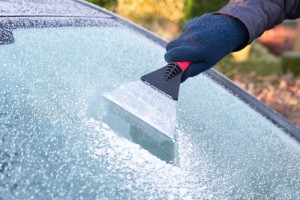 Scraping ice from windshield
